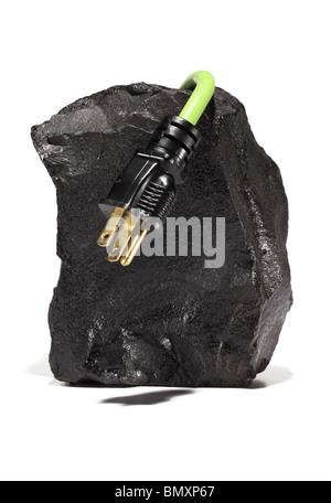 Ein großes schwarzes Stück Kohle eine grüne elektrische Verlängerungskabel mit Stecker umwickeln auf weißem Hintergrund. - Stockfoto