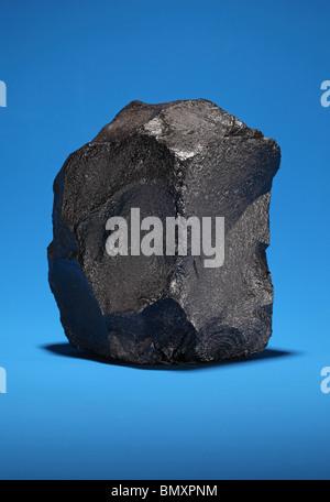 Ein großes Stück bituminöse Steinkohle auf einem leuchtend blauen Hintergrund - Stockfoto