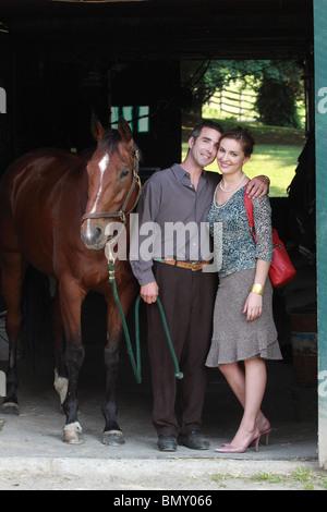 junges Paar mit Pferd im Stall - Stockfoto