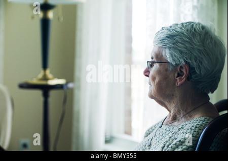 Profil der alten Frau im Sessel, Blick geradeaus. - Stockfoto