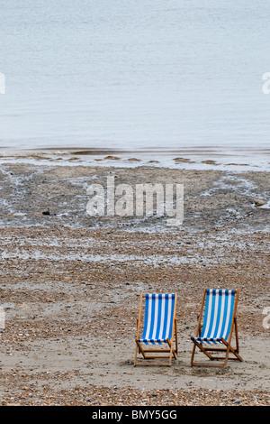 Zwei leere Liegestühle am Strand. - Stockfoto