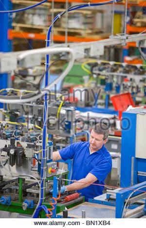 Arbeiter, die Bedienung von Maschinen auf Produktionslinie im Werk, das Aluminium Leuchten herstellt - Stockfoto