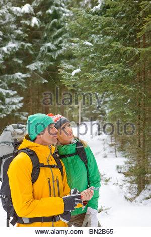 Paar mit Rucksäcke mit Kompass im verschneiten Wald - Stockfoto