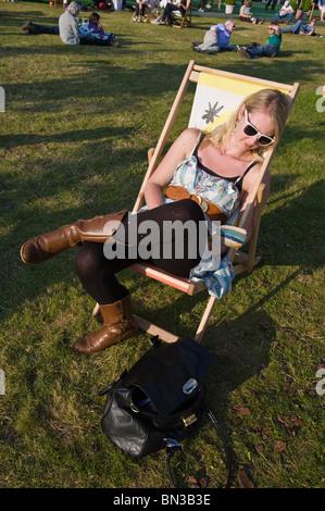 Trendige junge Frau Buch im Liegestuhl in der Sonne bei Hay Festival 2010 Hay on Wye Powys Wales UK sitzen - Stockfoto