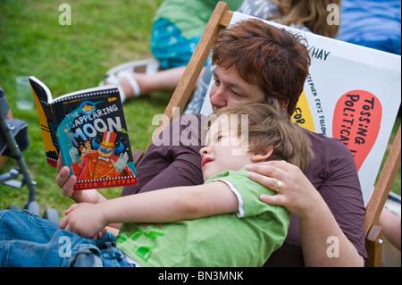 Mutter Lesebuch zu ihrem Sohn beim Sitzen im Liegestuhl bei Hay Festival 2010 Hay on Wye Powys Wales UK - Stockfoto