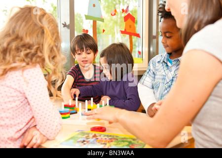 Kindergärtnerin, spielende Kinder - Stockfoto