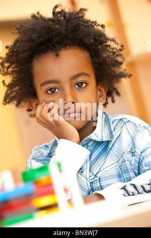 Kleiner Junge sitzt mit Hand am Kinn, Porträt - Stockfoto