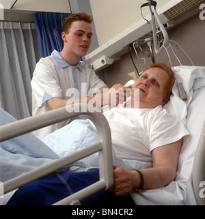 Verärgert Patienten im Krankenhaus und Trainee Student Überprüfung Ohrtemperatur von Frau in einstellbaren Krankenhausbett - Stockfoto