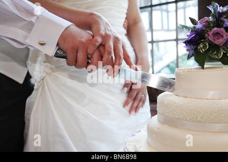 Braut und Bräutigam halten Messer und schneiden Hochzeit weiße abgestufte Kuchen am Tag der Hochzeit UK - Stockfoto