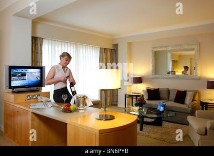 Hyatt Hotel, Birmingham, West Midlands, England, UK. Frau in der Hotel-Suite, eine Flasche Wein öffnen - Stockfoto