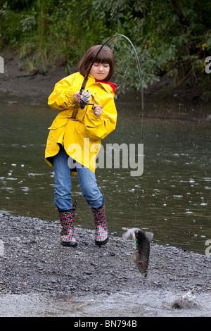 Junges Mädchen Spin Angeln auf Ingram Creek Rollen in einem rosa Lachs, Alaska - Stockfoto