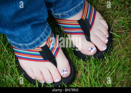 Pedikürten Zehen zeigen rote, weiße und blaue Sterne Aufkleber in bunte Flip-Flops am 4. Juli. - Stockfoto