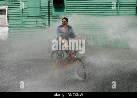 Eine junge Teen reitet durch das Spray von einer offenen Hydranten während einer Hitzewelle in New Haven CT USA - Stockfoto