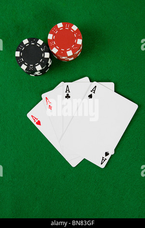 Vier Asse mit Poker-Chips am grünen Tisch. - Stockfoto