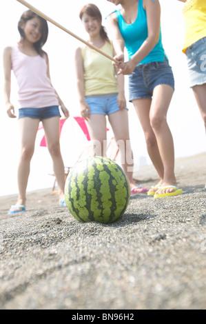 Vier Freunde schlagen eine Wassermelone mit einem Stock zu brechen Es shonan Präfektur Kanagawa Japan - Stockfoto