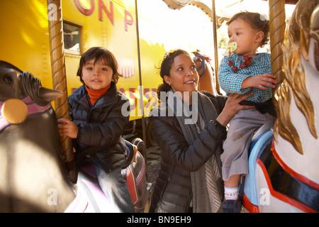 Mutter und Kinder freuen sich über Karussellfahrt - Stockfoto