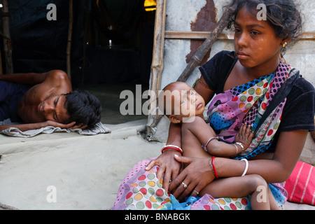 Eine junge Frau mit ihrem Kind in einem Slum am Stadtrand von Kolkata, Indien - Stockfoto