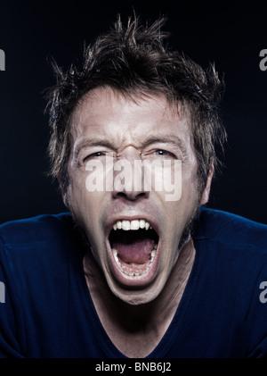 Studio-Porträt auf schwarzem Hintergrund für eine lustige expressive kaukasischen Mann schreien - Stockfoto