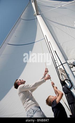 Vater und Sohn ziehen Seil auf yacht - Stockfoto