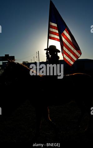 Cowgirl, die amerikanische Flagge winken PRCA Rodeo Event in Texas, USA - Stockfoto