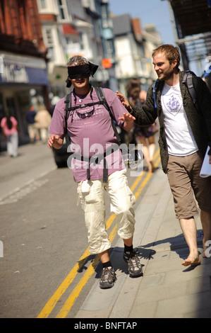 Führt einen Mann trägt eine Augenbinde durch die Straßen von Aberystwyth in einer Übung, die Erreichbarkeit der - Stockfoto