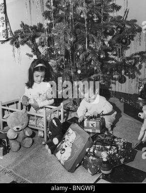 Mädchen spielen mit einer Puppe und ihr Bruder öffnen ein Weihnachtsgeschenk neben ihr, 1960er Jahre - Stockfoto