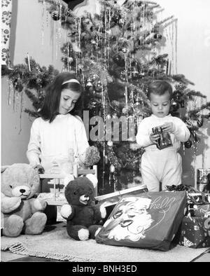 Mädchen spielen mit einer Puppe und ihrem Bruder ein Weihnachtsgeschenk neben ihr öffnen - Stockfoto
