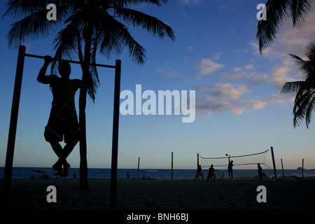 Ein Mann arbeitet auf einer Fitness-Station als Silhouette gegen den späten Nachmittag Himmel ein Beach-Volley-Ball-Spiel stattfindet.