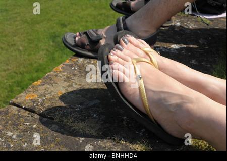 Paar Damen Füße mit lackierten Zehennägeln in Flip-Flops im Sommer - Stockfoto