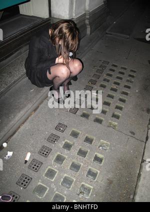 Betrunken Frau sitzt auf Bürgersteig in der Nacht - Stockfoto