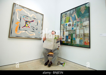 Ein Wachmann an Pallant House Art Gallery, Chichester, West Sussex, liest The Sunday Telegraph vor einem Peter Blake - Stockfoto