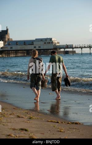 Rückansicht eines jungen Paares, zu Fuß entlang des Strandes an der Aberystwyth Wales Großbritannien an einem Sommerabend - Stockfoto