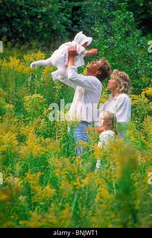 Vierköpfige Familie im Gebiet der wilden gelben Blüten in Schweden - Stockfoto
