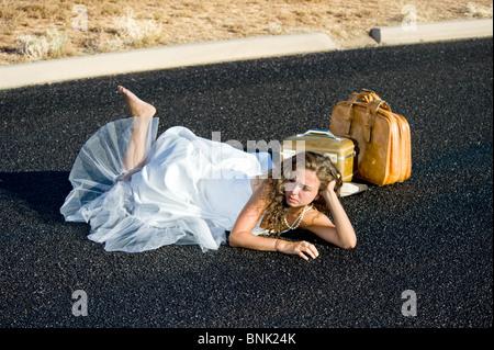 Eine Braut wird gekickt an den Straßenrand und ganz allein auf einer abgelegenen Straße. - Stockfoto