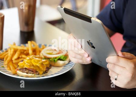 Ein Mann liest Online-News aus seinem iPad in der Mittagspause - Stockfoto