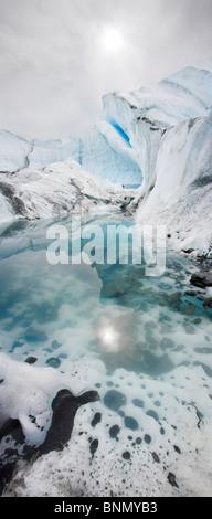 Sonne spiegelt sich in einem Pool von Gletscherwasser mit Eis Flossen auf dem Matanuska Gletscher, Alaska