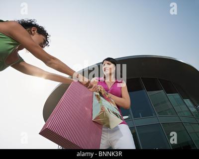 zwei Frauen streitenden Einkaufstaschen aus Einkaufszentrum. Horizontale Form, niedrigen Winkel Ansicht, Textfreiraum - Stockfoto