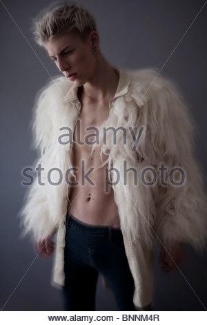 blonde junge mit Piercings, die von der Kamera Weg suchen. Er trägt eine pelzige Jacke mit seiner Brust sichtbar. - Stockfoto
