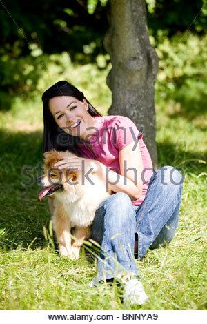 Eine junge Frau sitzt auf dem Rasen, streichelte ihr Hund - Stockfoto