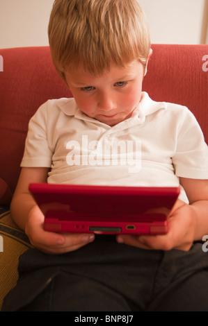 Ein MODEL-Release Nahaufnahme Bild eines sechsjährigen Jungen spielen auf einem Nintendo DS handheld Computer Spielkonsole - Stockfoto