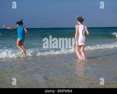 Zwei Mädchen spielen in Wellen am Strand - Stockfoto