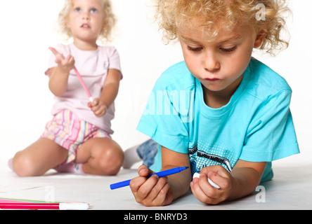 weibliche und männliche blonde kaukasische entzückende Kinder spielen mit Farbe Stifte - Stockfoto