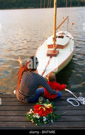 Mutter und Kind sitzt auf hölzerne dock mit Ankern Segelboot und Teller mit Flusskrebsen, Kerzen und Aquavit in - Stockfoto