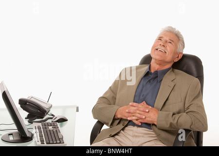Geschäftsmann entspannend an seinem Schreibtisch - Stockfoto