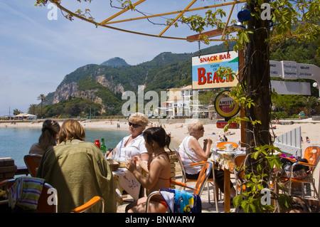 Touristen genießen Mittagessen in der Snackbar am Strand bei Paleokastritsa auf der griechischen Insel Korfu Griechenland - Stockfoto