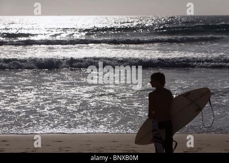 Eine Surfer schaut auf die Wellen am Manly Beach. Sydney, New South Wales, Australien - Stockfoto