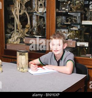 Junge im sitzen am Tisch im museum Stockfoto