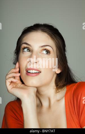 Junge Frau nachdenklich wegsehen, Porträt - Stockfoto
