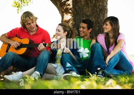 Junger Mann sitzt mit Freunden unter Baum, Gitarre spielen - Stockfoto