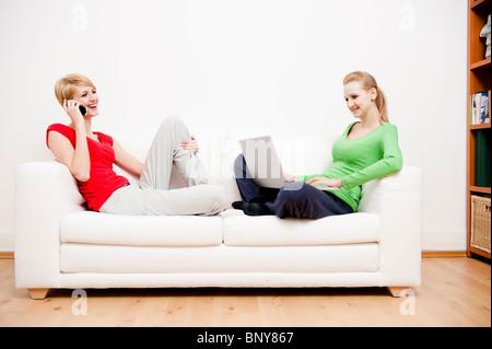 Zwei Frauen, die mit Laptop und Handy auf sofa - Stockfoto